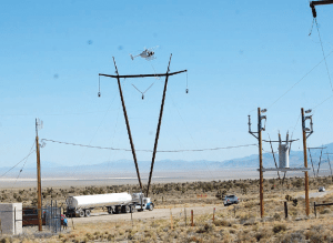 Helicopter strings center line on tower for the new NV Energy power line as it begins to cross over U.S. Highway 93 in Dry Lake Valley. The 235-mile line will connect the Harry Allen Substation north of Las Vegas with the Robinson Summit Substation 20 miles east of Ely. (Dave Maxwell photo)