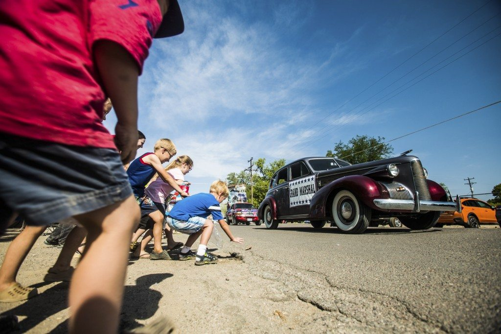 Children grab candy tossed as the grand marshal?s car goes by.
