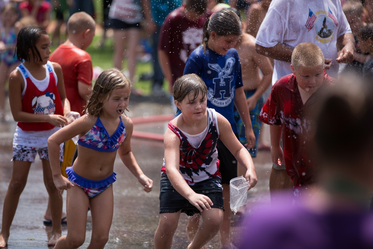Local children gather for the water spray to cool down and catch some change. (Photos courtesy John Deitrich)