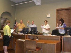 City Clerk Jo Whitlock, front, has the new council members recite their oath to office. From left, Steve Rowe, Cody Christensen, Mayor Stana Hurlburt and JoLyn Cardinal comprise the new council elected. (Rachel Williford photo)