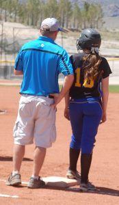 Pahranagat first base coach Dave Hansen talks with Allyse Frehner. Pahranagat Valley plays a doubleheader today at Indian Springs to close out the regular season, then will host the league tournament May 12-14 in Alamo. Photo by Dave Maxwell.